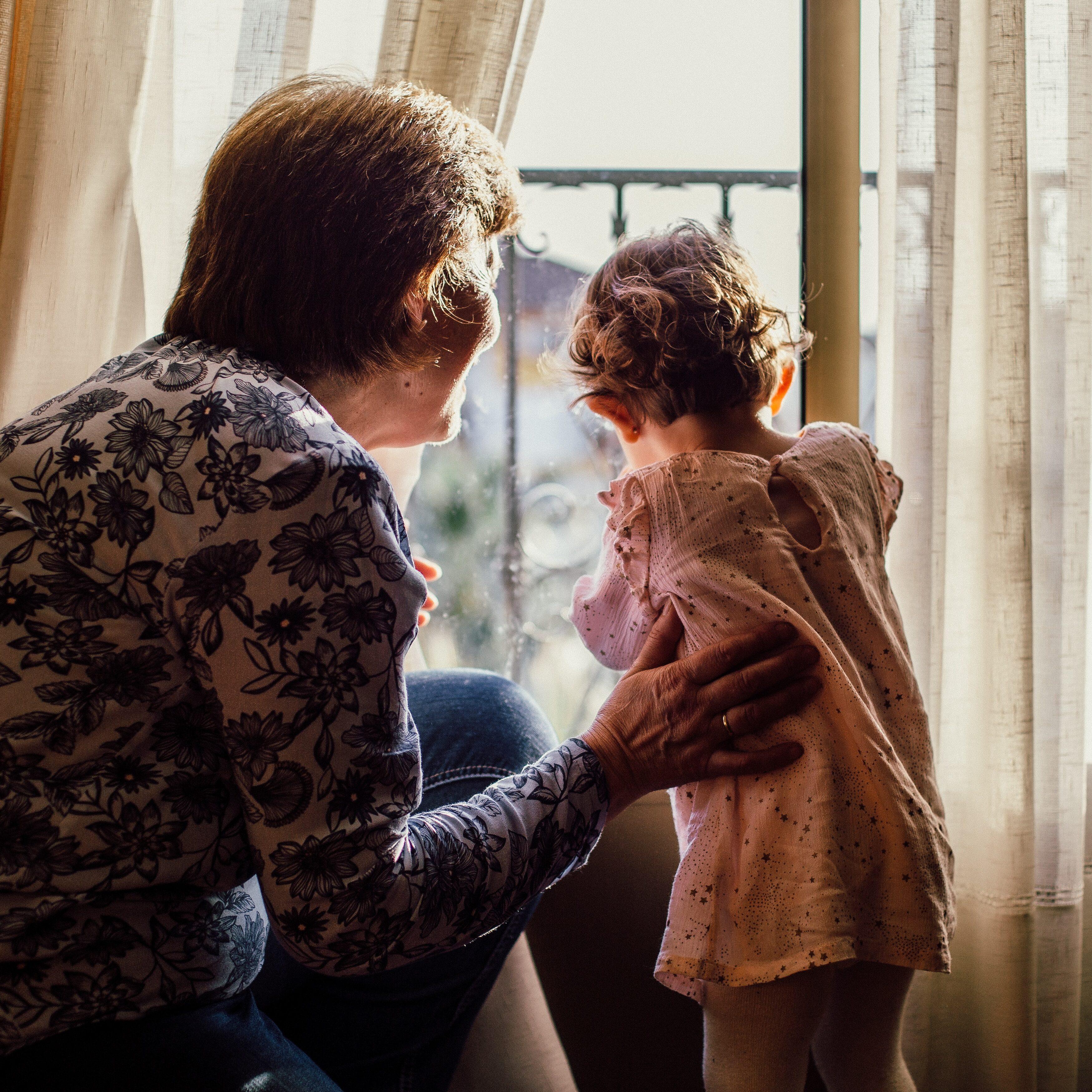 woman-holding-baby-near-window-1109238
